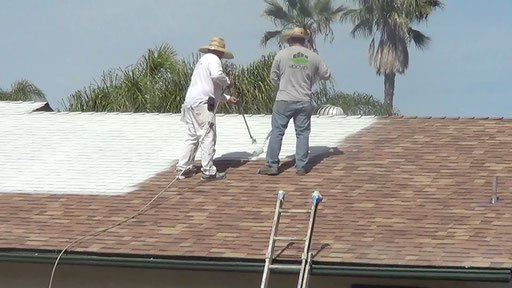 Two workers adding a roof coating for improved roof protection